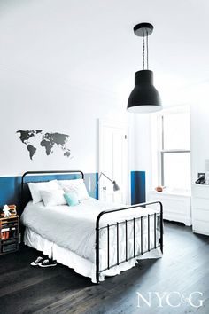 Guest bedroom with world map decal on wall and industrial light