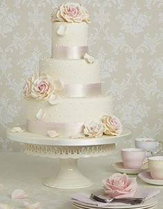 Modern take on a class cream and blush cake featuring fat blush ribbon and tiny pearl decorations.