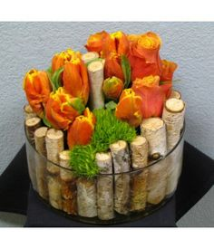 Unique arrangement with Cherry-Brandy Roses and Orange Tulips with Yellow Tip, Green Trick and Birch Stumps in a low glass cylindar vase...