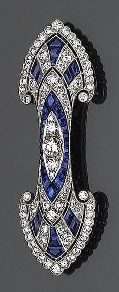 A late art deco sapphire, diamond and platinum brooch the double fan-shaped brooch centering a European-cut diamond, accented by calibré-cut sapphires and transitional round brilliant-cut diamonds