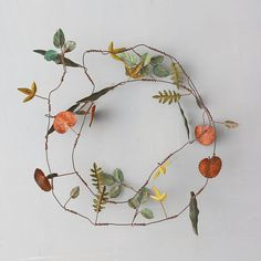 """Metal leaves in an assortment of shapes and polished hues adorn this delicate strand for sprucing up natural décor.- Metal, wire- Wipe clean with damp cloth- Indoor or sheltered outdoor use- Imported3""""W, 69""""L"""