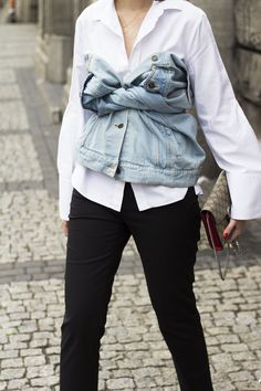 For a new styling trick, layer your denim jacket over a white button-down shirt and tie the sleeves as a top
