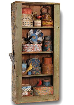 SMALL ANTIQUE WALLPAPER BOX COLLECTION AND BIRD PINCUSHIONS LINE THE SHELVES OF THIS ANTIQUE SHELF IN CHIPPY PAINT.