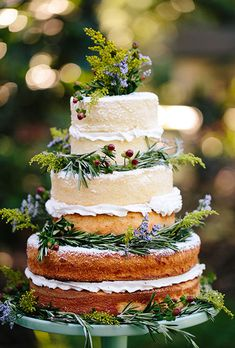 Brides.com: . A rustic, three-tiered naked cake with fresh greenery and berry accents, created by Delliquez Custom Cakes N' Catering.