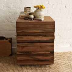 """Rugged and relaxed. With drawer fronts crafted of solid saal wood, our Stria Nightstand's raised relief pattern highlights the natural grain of the wood and eliminates the need for hardware on its drawers. With its natural imperfections and color variations, each piece is subtly unique.  * 18""""sq. x 23""""h.  * Solid saal wood drawer fronts.  * Frame made of mango wood, acacia and engineered wood.  * Honey finish.  * Natural variations in the wood grain and coloring are to be expected.  * Two…"""