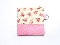 A small, cute coin purse made out of cotton fabrics. Its flat and can easily fit into your main bag, and can store all those easy-to-lose items like coins and keys and travel cards. It makes a great gift card holder, too.  The main outer part of the pouch features a light yellow fabric with roses in shades of pink and red. The accent is a dusky pink fabric with small white dots. The outside layer is interfaced to keep it stable. Inside, it is completely lined with a light brown fabric with…
