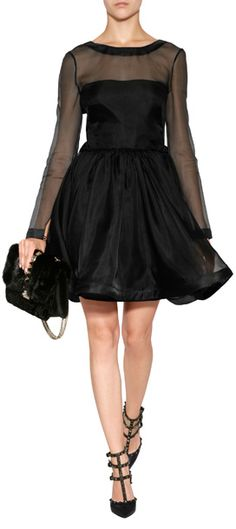 A fun flounce skirt lends an impossibly flirty look to this sheer sleeve silk dress from Valentino / Sheer black silk top and long sleeves, round neckline, bow detailed back with hidden zipper underneath / Tailored top, full flounce skirt / Wear with bright pink lipstick and pointy toe pumps #Stylebop