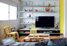 Na sala deste apartamento de 120 m², a parede de madeira de demolição é a estrela. Sobre a prateleira, garrafas compõem um pequeno bar e um pôster do filme Blow-Up, do italiano Michelangelo Antonioni. Projeto do arquiteto Guto Requena