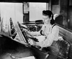 A switchtender on the Pennsylvania Railroad helping to classify freight trains at a large eastern freight yard. The electric controls on the board actuate rail switches in the yard. She is taking the