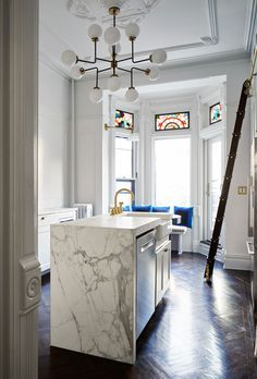 Samantha and Jonah Arcade'sPark Slope brownstone is the perfect balance between new and vintage, or historic and modern. Really, anytime we have an excuse for a library ladder we're happy! This beautiful kitchen island, with marble that reachesallthe way down to the floor, also has a dishwasher and stunningbrass faucet for the sink.