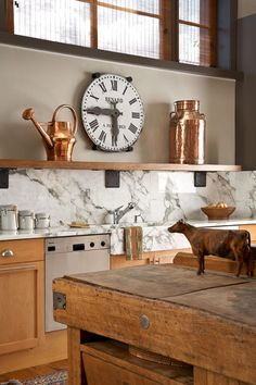 White marble counter tops. Antique copper items.Vintage French railroad clock.