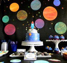Painel com planetas ao fundo e o bolo cenográfico estão d+.