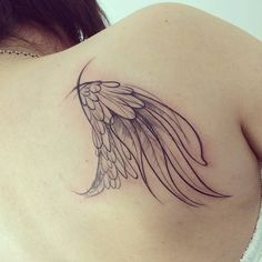 Sketch work style wing tattoo on the right shoulder blade.