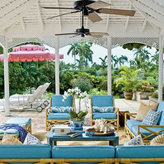 Sleek Blue;   Rattan furniture, pretty blues, and a burst of pink give this outdoor living room a modern yet retro feel. The organic outdoor fabric allows the space to withstand island heat, wind, and rainstorms.