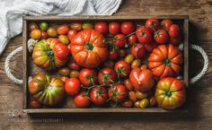 Pic: Colorful Heirloom tomatoes in rustic wooden tray over dark background
