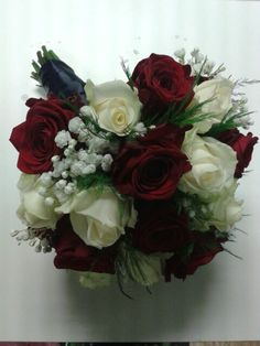 Red Naomi roses with ivory Avalanche roses, gypsophila, and tree fern, creating a bridal bouquet.