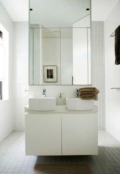 Très design, ce meuble suspendu au milieu de la salle de bain, surmonté d'un immense miroir - et un passage de part et d'autre. Même mosaïque rectangulaire au sol et aux murs.