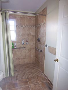 Customer had MARJOS remove the tub and the new tile shower now has no curb to allow for customer's wheelchair access.  Additional grab bars added, extra blocking behind walls for securing, to allow movement throughout the entire shower.