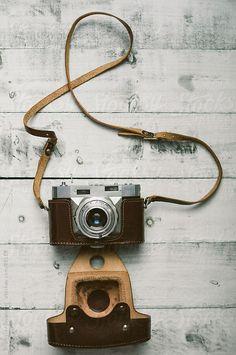 Retro camera on a wooden background by Branislav Jovanović