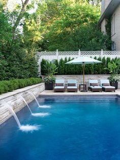 Timeless built-in swimming pool with stone wall and white chaise lounge chairs and patio umbrella.
