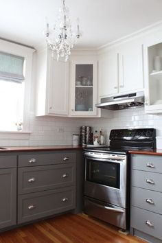 Two Tone cabinets. hate the light fixture. simple shaker doors with knobs and pulls. wood floor, counter top