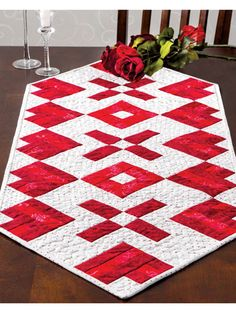 """Romantic table runner featuring some hugs and kisses!   Stitch up a romantic table runner and have it on hand for a spontaneous quiet evening dinner. This e-pattern was originally published in the Spring 2014 issue of  Quilter's World  magazine. Finished size is 44 5/8"""" x 19 1/8""""."""