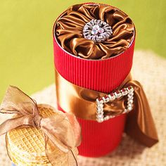 Start at the Top: a simply cylinder looks picture perfect thanks to a pinwheel of ribbon folded and tucked into the top. Add a rhinestone buckle threaded with satin ribbon around the center of the package.