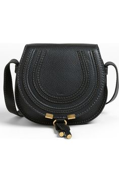 Curvaceous detailing ornaments the saddle-shaped flap of a luscious crossbody crafted from sumptuous grained leather.
