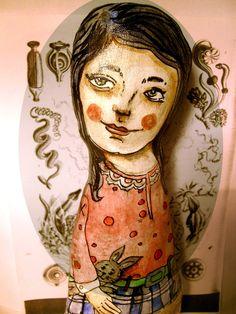 """""""Mädchen mit den Hasen"""" ist eine Skluptur gemacht aus Stoff, es ist bemalt und lackiert und steht auf einen Holzstück, dass beklebt mit schönen Papier"""