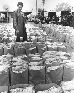 Bobby Seale looking over bags of food being donated to the black community, 1972.