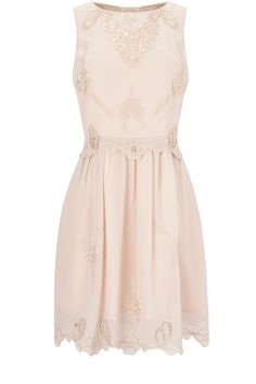 This sleeveless tunic style dress has cutwork embroidered detailing to the body and a raw edge hem.