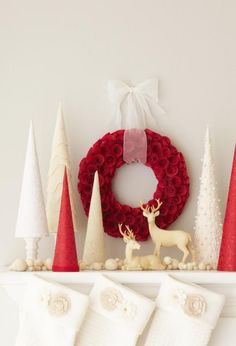 """A rosy wreath makes the perfect backdrop to this elegant winter vignette. Create a faux forest by wrapping festive paper and cloth over foam cones; hot-glue to secure. Usevarying sizes of felt balls for """"snow."""""""