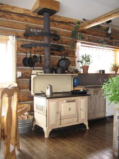 The wood cook stove. Love how the cast iron is hung around the stove. I want a wood cook stove Decor, Vintage Stoves, Wood Stove Cooking, Home, Rustic Cabin, Vintage Kitchen, House Interior, Log Cabin Kitchens, Rustic House