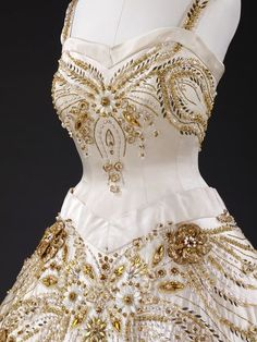 Lavish gold and white beadwork encrusts this ivory evening dress worn by Queen Elizabeth II on a state visit to Paris in 1957. The dazzling, jewel-like details of the embroidered design include miniature bees, grasses, wheat and wild flowers. These motifs are worked in relief in faceted glass, gold beads, brilliants and variously shaped pearls, mother-of-pearl and gold petals