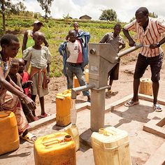 People from Gistore, Rwanda, pump water at their charity: water project.