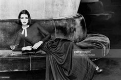 Model Janice Dickinson, seated on circular banquette with a cocktail drink, wearing a black silk chiffon full-length dress with ribbon of rhinestones at the neck by Lanvin