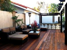 Designer Claudia Schmutzler uses redwood to create a stunning deck and pergola, transforming the typical backyard into a outdoor retreat perfect for entertaining.