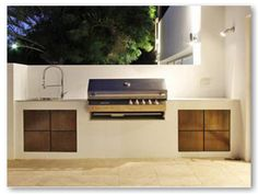 Outdoor built-in grill, counter and sink, brightly lit with selectively directed lighting.