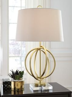 Fall in love with the Axi Gold Finish Metal Table Lamp by Signature Design by Ashley at Direct Value Furniture proudly serving Roscoe, IL and surrounding areas for over 10 years! Sale Table, Metal Table Lamps, Signature Design By Ashley, Table Lamp, Crystal Table Lamps, Best Desk Lamp, Gold Table Lamp, Lighting Trends, Pure Decoration