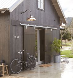 check out these Copper Barn lights. Barn style home with exterior barn doors and copper barn lights. Lighting is Rejuvenation Carson Gooseneck Photo By Rejuvenation