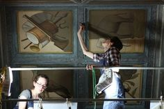 """Anne Schaffer, graduate conservation student, left, and Andrea Chevalier """"inpaint"""" the ceiling moldings and clean the coffer panels on the ceiling of the King Sculpture Court at the Allen Memorial Art Museum."""