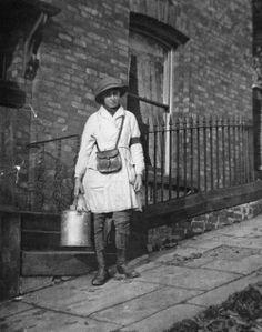 A milkwoman delivering milk door to door during World War I. United Kingdom, 1917.