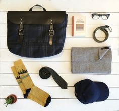 The men's staples we're loving this fall: our plaid and leather messenger bag, cozy gray textured scarf, gray flannel tie, yellow patterned socks, and navy blue baseball cap | Banana Republic