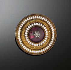 A Victorian gold, garnet and diamond brooch  Of Etruscan revival style circular design, with central cabochon garnet and rose cut diamond boss centre, within stepped border with white enamel petal and bead and wirework detail decoration, with locket back, circa 1870