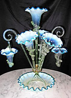 A rare and unusual Stourbridge Victorian art glass epergne, This model has 5 fluted tulips with two glass canes with hanging baskets. The condition is excellent, the glass appears to be clear however, when photographing it, there is a definite vaseline tint to the glass, & rigoree, all the glass is trimmed in an unusual blue. 20 inches tall and 16 inches wide
