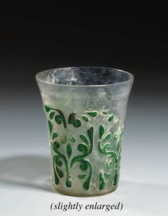 AN ABBASID GREEN AND CLEAR GLASS FRAGMENTARY CAMEO BEAKER   PROBABLY SAMARRA, MESOPOTAMIA, 8TH/9TH CENTURY   Of slightly flaring cylindrical form, the sides with a broad band of four panels each with a central stem issuing split palmettes and arabesques cut through the green outer glass surface to the inner clear glass body, areas of restoration  4¼in. (11cm.) high