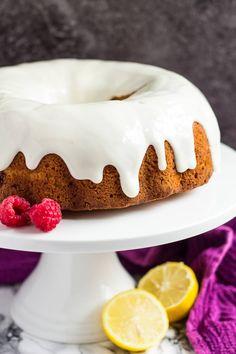 Lemon raspberry bundt cake with a thick lemon glaze on a white cake stand.
