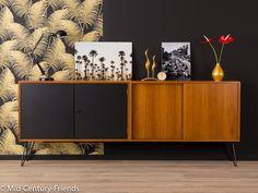 Klassisches Sideboard aus den 1960er Jahren. Hochwertiger Korpus in Nussbaum Furnier mit zwei resopalbeschichteten Schranktüren in schwarz, zwei Schiebetüren in Teak und neuen, zeittypischen...