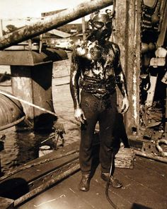 A diver as he ascends from the oily interior of the sunken battleship USS Arizona (BB 39) . Photograph released May 23, 1943.