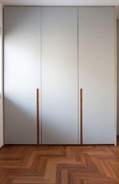Na imagem, é possível ver os detalhes das portas dos armários dos quartos da crianças, revestidas com laminado melamínico cinza claro com cavas de madeira. O projeto é do arquiteto Renato Dalla Marta, do escritório AUM
